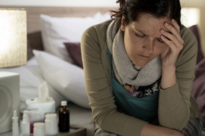 Ill woman with medicines suffering from flu headache in bedroom