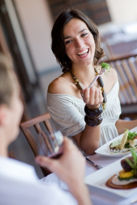 A young woman laughing whilst eating dinner at a restaurant